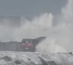 man driving on jetty during big waves